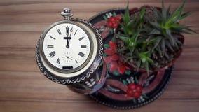 Klockan på den wood bakgrunden och blomman Royaltyfri Bild