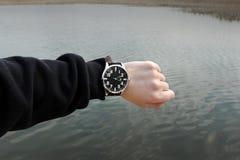 Klockan p? handen p? bakgrunden av vatten fotografering för bildbyråer