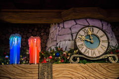 Klockan på spiselkranens bredvid en kugge med stearinljus Royaltyfri Fotografi