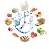Klockan som är ordnad från sunda livsmedelsprodukter, plaskar vid vatten som isoleras på vit bakgrund sund begreppsmat Royaltyfria Bilder