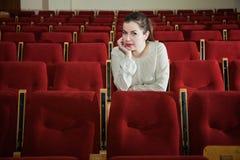 Klockashow för ung kvinna i tom teater eller biokorridor Arkivbilder