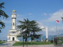 Klockatorn och nationsflagga av Georgia på sjösidan i Batumi, Black Sea strand Royaltyfria Foton