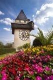 Klockatornet (Uhrturmen) och blommaträdgård Österrike graz royaltyfri fotografi