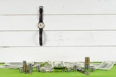 Klockor, mynt och dollar på trätabellen på ljus bakgrund Arkivbilder