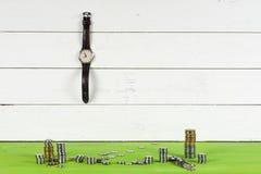 Klockor, mynt och dollar på trätabellen på ljus bakgrund Fotografering för Bildbyråer