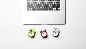 Klockor och bärbar dator Arkivbild