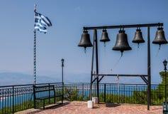 Klockor och grekisk flagga på helgonet Patapios av den Thebes kloster, Loutraki, Grekland Royaltyfria Bilder