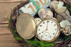 Klockor, pengar och ägg i ett rede Royaltyfri Bild