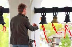 Klockringaren som ringer de kyrkliga klockorna royaltyfri bild