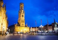 Klockstapel av Bruges och Grote Markt på natten arkivbilder