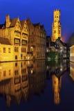Klockstapeln av Bruges reflekterade i kanalen Arkivfoto