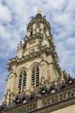 Klockstapeltornet av det gotiska stadshuset i den franska stadsarrasen på en blå himmel med vit fördunklar bakgrund, världsarv vi Arkivbild