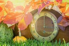 Klok in de herfstbladeren met pijl als symbool voor tijdverandering in de wintertijd stock afbeeldingen