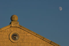 Klok die in de bouw met blauwe hemel & Maan wordt geplaatst stock fotografie