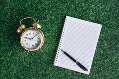 Klok en leeg notitieboekje op een groen gras stock afbeelding