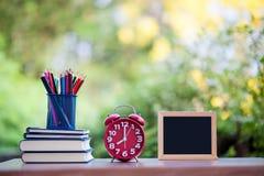 Klok en notitieboekje met potlood stock foto