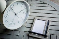 Klok en notitieboekje op houten lijst Royalty-vrije Stock Foto