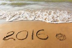 Klok, het jaar van 2016 op zandig strand wordt geschreven dat Royalty-vrije Stock Foto's