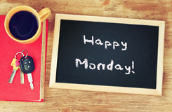 Klok, koffiekop en bord met de uitdrukkings gelukkige maandag! Stock Afbeelding