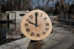 Klok met houten boomstam stock afbeeldingen