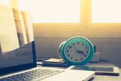 Klok met Laptop op bureau en zonneschijn in middag royalty-vrije stock afbeeldingen