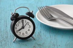 Klok met vork en mes op plaat stock fotografie