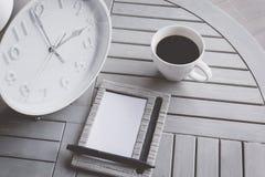 Klok, notitieboekje en een kop van koffie op houten lijst Stock Afbeelding