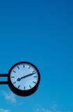 Klok op blauwe hemelachtergrond stock foto's