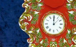 Klok op een rode achtergrond met een helder bloemenpatroon royalty-vrije stock foto