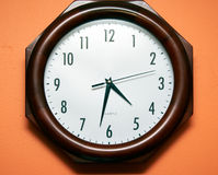 Klok op oranje muur Royalty-vrije Stock Foto's