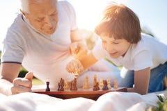 Klok trevlig man som uppmuntrar hans barnbarn som spelar schack Fotografering för Bildbyråer