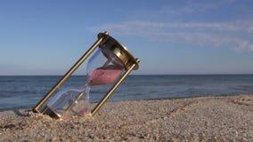 Klok van de messings de oude zandloper sandglass op overzees strandzand stock videobeelden
