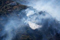 Klok 212 van de vuurleidingshelikopter dalingenwater op het brandende hieronder land Tussen Sayalonga en Arena's, Andalucia, Span Stock Afbeelding