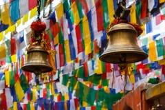 Klokken en boeddhistische het bidden vlaggen in tempel stock foto