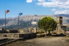Klokketoren van Gjirokaster-Citadel naast vlaggestok met Albanese en Europese vlag - een goed-bewaarde Ottomanestad, Albanië stock afbeelding