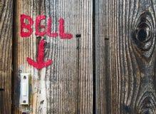 Klokteken die aan een deurbel op houten muur richten Stock Fotografie