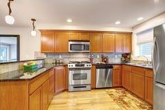 Klonowi kuchenni gabinety z stalowymi urządzeniami i granitów wierzchołkami zdjęcia stock