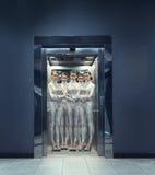 Klony młode kobiety w srebnej futurystycznej kostiumowej pozyci w windzie Fotografia Stock