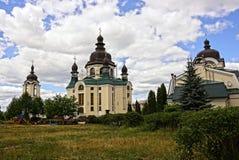 Kloosters en kerken in een groen park tegen de hemel en de wolken stock foto