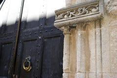 Kloppers op een oude deur en een kolom Stock Foto