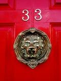Kloppers op rode deur nummer 33 met dierlijk gezicht Stock Foto