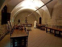 Kloster av St Michael i Frigolet, Frankrike - kan 28, 2017: En munk i en vitkaftan ställer in tabellen i matsalen av en ancie arkivfoton