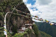 Kloster Taktsang Palphug mit Gebetsflagge (alias der Tigernesttempel), Paro, Bhutan Lizenzfreies Stockbild