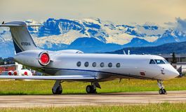 Gulfstream V airplane at the Zurich airport. Kloten, Switzerland - May 4, 2015: a Gulfstream V airplane at the Zurich airport, summits of the Alps in the Royalty Free Stock Photography
