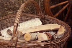 Klotz liegen in einem Weidenkorb mit einem Griff auf dem Hintergrund von Heuschobern stockbild