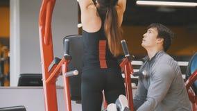 Klub - młoda kobieta wykonuje UPS z samiec trenerem - tylni widok, zakończenie up zdjęcia royalty free