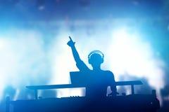 Klubba diskodiscjockey som spelar och blandar musik för folk uteliv Arkivfoto