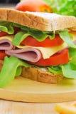 Klubbasmörgås med ost, den inlagda gurkan, tomaten och skinka gar Arkivfoto