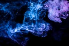 Klubbor av kulör rök av blå och rosa färg på en svart bakgrund i form av mjuka moln från vape arkivbilder