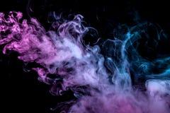 Klubbor av kulör rök av blå och rosa färg på en svart isolerad bakgrund i form av mjuka moln från vape arkivbilder